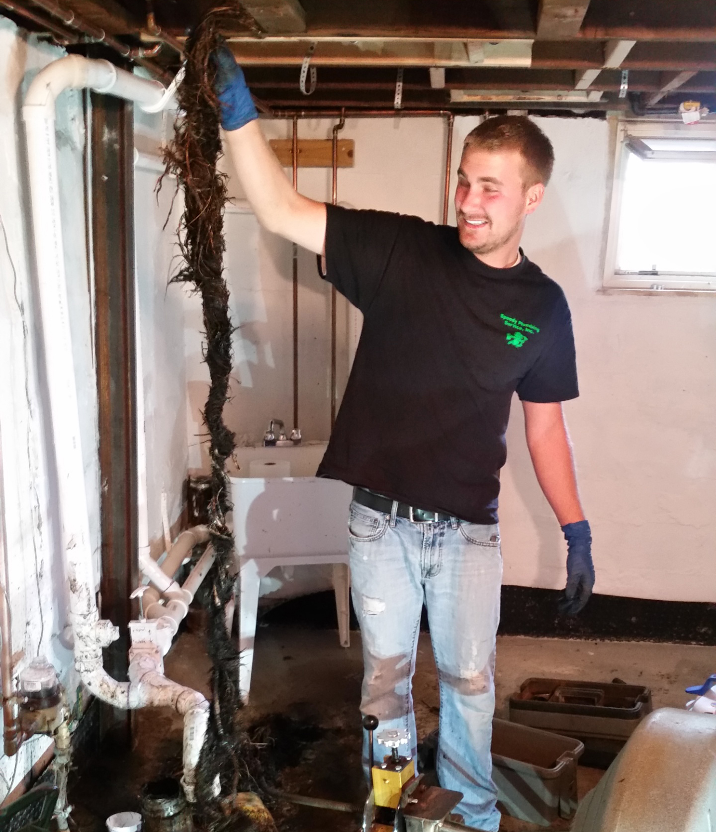 Speedy Plumbing employee unclogging drain